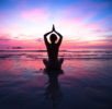 Sunset yoga woman on sea coast.