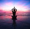 Sunset yoga woman on sea coast.